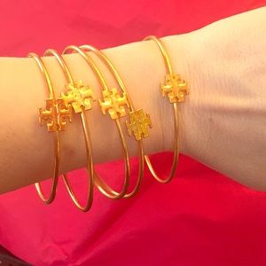 Five gold colored Tory Burch bangles